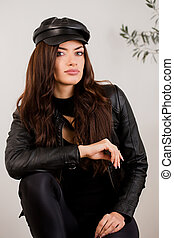 Beautiful woman in a leather jacket and cap