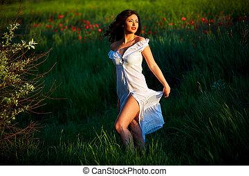 Beautiful woman in a poppy field with flowers