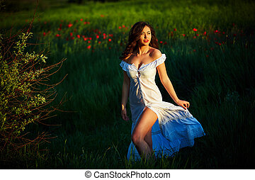 Beautiful woman in a poppy field with flowers