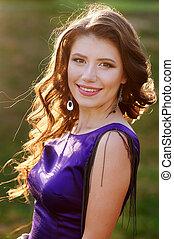 beautiful woman in a purple dress on the meadow