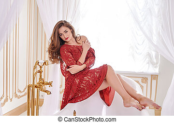 Beautiful woman in a red dress in the bathroom