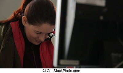 Beautiful woman in a red jacket looks in optical microscope, computer screen.