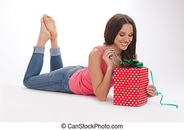 beautiful woman in a red t-shirt and blue jeans enjoys gift on Valentine's day