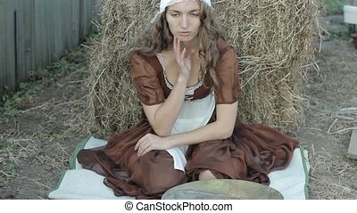 beautiful woman in a rustic dress sits on a hay and sifts the grain
