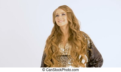 Beautiful woman in a shiny dress and with long hair singing in the studio, on a white background.