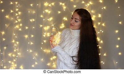 Beautiful woman in a warm white sweater holds in hands a...