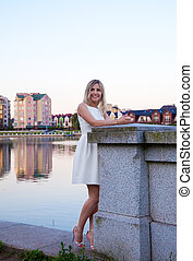 beautiful woman in a white dress standing on the waterfront