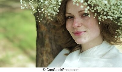 Beautiful woman in a white gown dress in the forest with flowers 4k