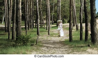 Beautiful woman in a white gown dress in the forest with flowers