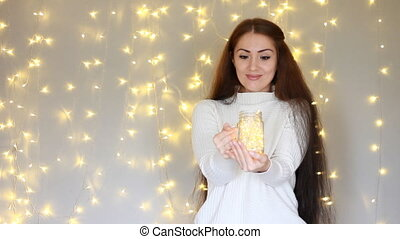 Beautiful woman in a white sweater holds in hands a lamp,...