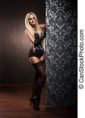 Beautiful woman in alluring lingerie posing near luxury...