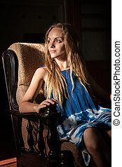 Beautiful woman in an old armchair