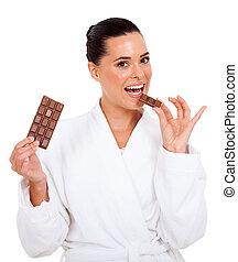woman in bathrobe taking a bite of chocolate