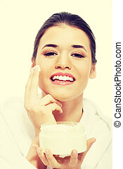 Beautiful woman in bathrobe with face cream