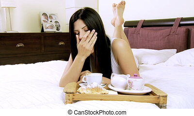 Beautiful woman in bed eating