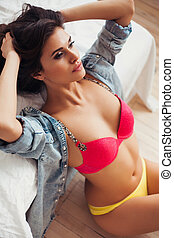 Beautiful woman in bedroom, wearing colorful lingerie and jeans shirt.