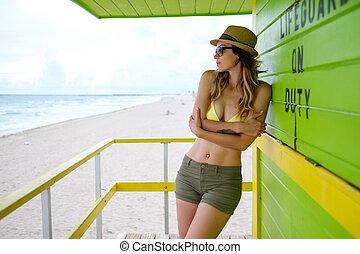 Beautiful woman in bikini at lifeguard station, Miami, USA -...