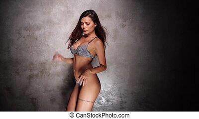 Beautiful Asian girl in bikini dancing sensually over concrete wall background in the studio
