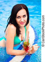Beautiful woman in bikini sitting in swimming pool with...