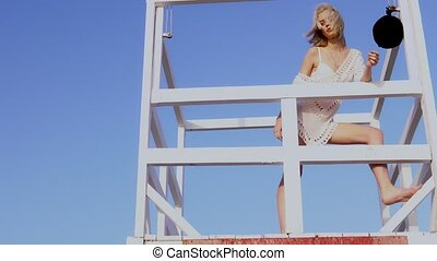 Beautiful woman in bikini standing at the lifeguard station, lifeguard tower. Young girl in swimsuit on the beach lifeguard tower looking into the distance against the sea.