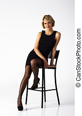 beautiful woman in black dress posing sitting on a chair