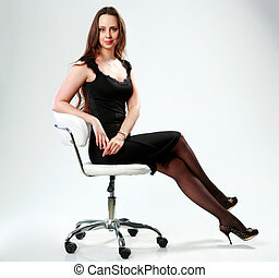 Beautiful woman in black dress sitting on the office chair over gray background