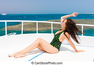 Beautiful woman in black-green swimsuit lying on the deck of the yacht at a sunny summer day