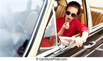Beautiful woman in black sunglasses sitting in the retro car...