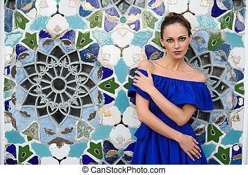 beautiful woman in blue dress looking at camera