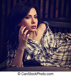 Beautiful woman in boyfriend shirt lying on the bed and thinking about life. Tender romantic portrait. Closeup. Toned vintage. Art