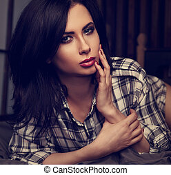 Beautiful woman in boyfriend shirt lying on the cozy comfortable bed and looking in camera. Tender warm romantic portrait. Closeup toned vintage. Art