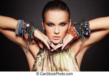 portrait of beautiful young brunette woman posing in rings and multiple bracelets on dark gray