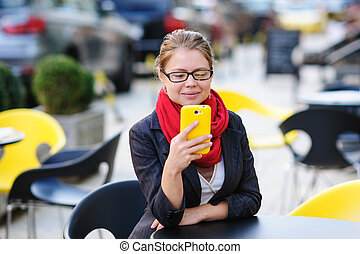 Beautiful woman in Cafe looks at phone