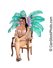 Beautiful woman in carnival costume sitting on chair