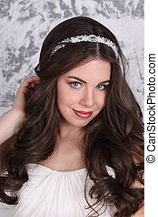 Beautiful woman in diadem and with hairdo poses in studio, close-up