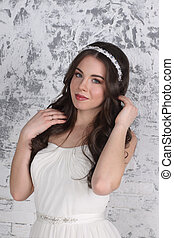 Beautiful woman in diadem and with hairdo poses in white studio