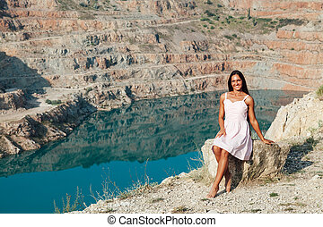 Beautiful woman in dress looks at the view of a mountain lake