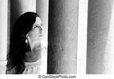 Beautiful woman in dress on the background of columns