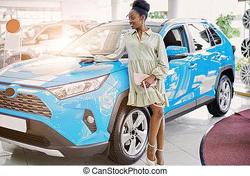beautiful woman in dress posing next to blue car