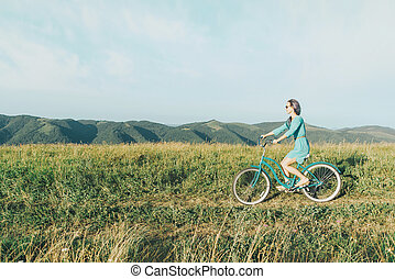 Beautiful woman in dress riding bicycle.
