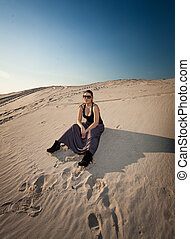 woman in dress sitting on sand dune
