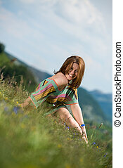 beautiful woman in dress sitting on the grass