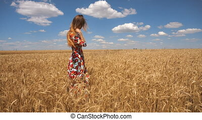 woman in dress stands in the middle of the field with wheat and straightens hair