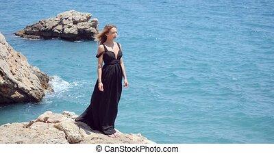 Beautiful woman in elegant black dress near the sea