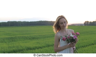 beautiful woman in field with flowers at sunset