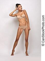 Beautiful woman in flesh color underwear. Studio shooting....