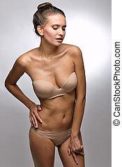 Beautiful woman in flesh color underwear. Studio shooting.