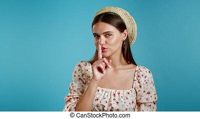 Beautiful woman in floral dress holding finger on her lips over blue background. Gesture of shhh, secret, silence. Close up. High quality 4k footage