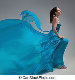 Beautiful woman in fluttering airy blue dress. Gray...