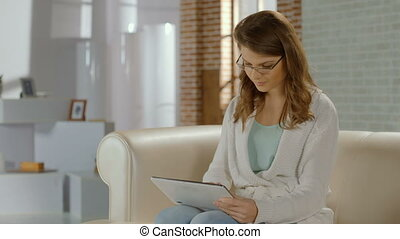 Beautiful woman in glasses enjoying work on tablet PC, browsing